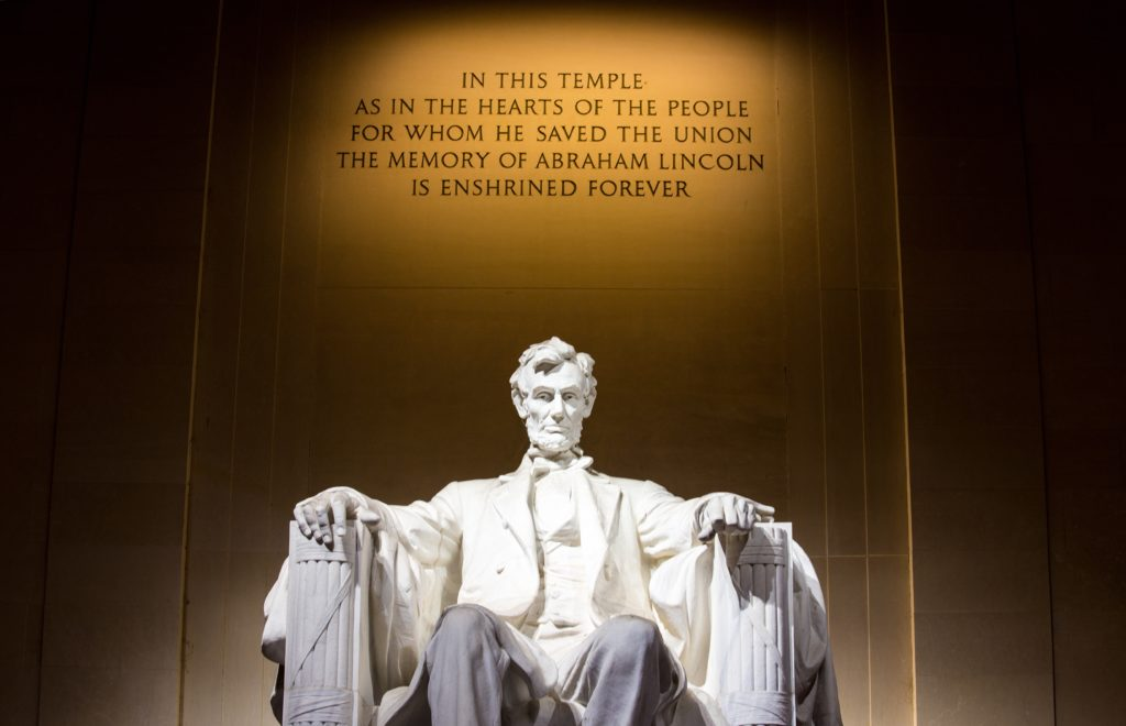 A man standing in front of a sign with Lincoln Memorial in the background